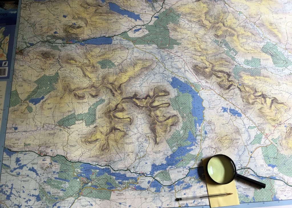 The EastWest Mapping Connemara Mountains map on a desk with a magnifying glass